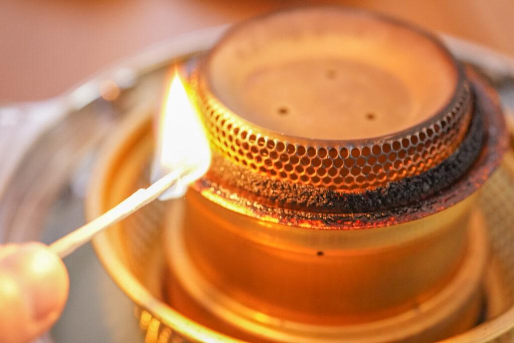 マッチをシュッってやって火をつけて、芯のところに火を移していきます。